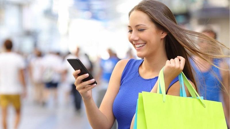 Mulher fazendo compras e usando o celular na Cidade do Cabo
