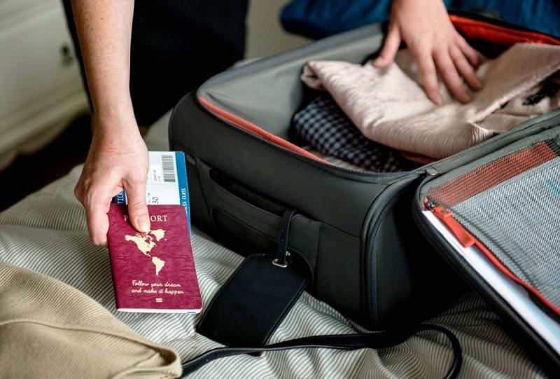 Pessoa arrumando mala com passagem e passaporte