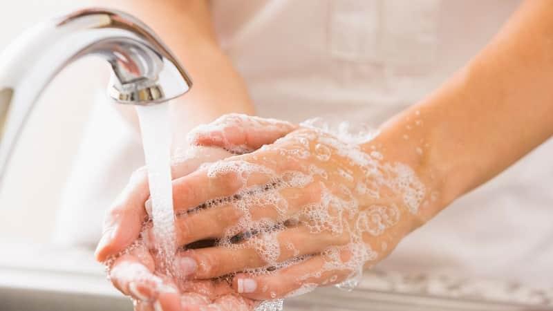 Pessoa higienizando as mãos