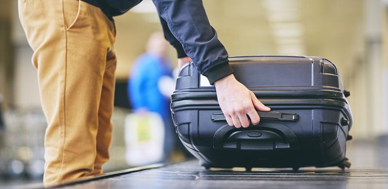 Homem pegando mala em aeroporto