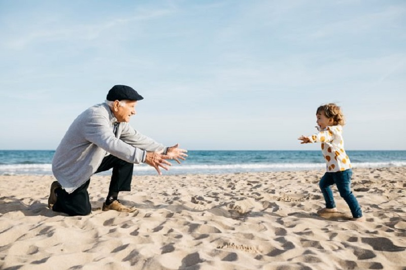 Avô e neta em praia